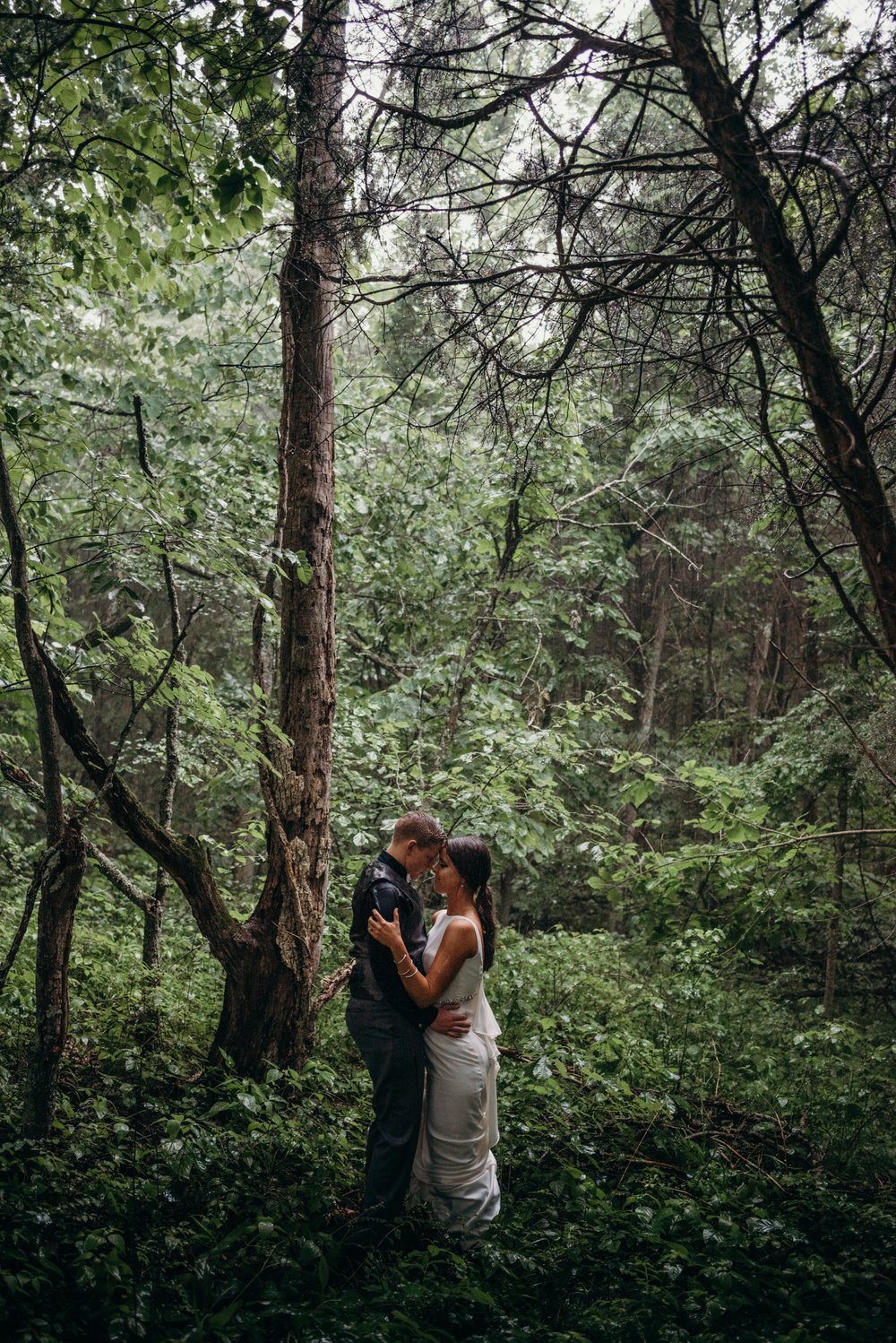 Two women embrace with foreheads touching in woods of Kentucky