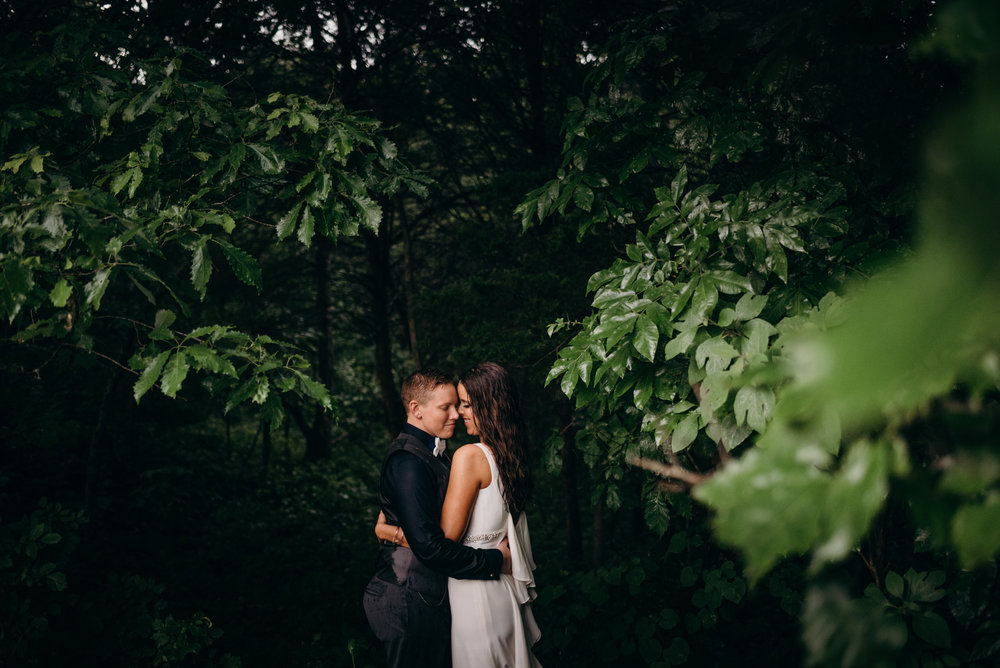 Brooke and Raychel smiling and embracing with eyes closed in Kentucky forest
