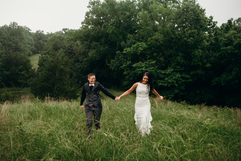smiling same-sex newlyweds holding hands and walking in Kentucky field in the rain