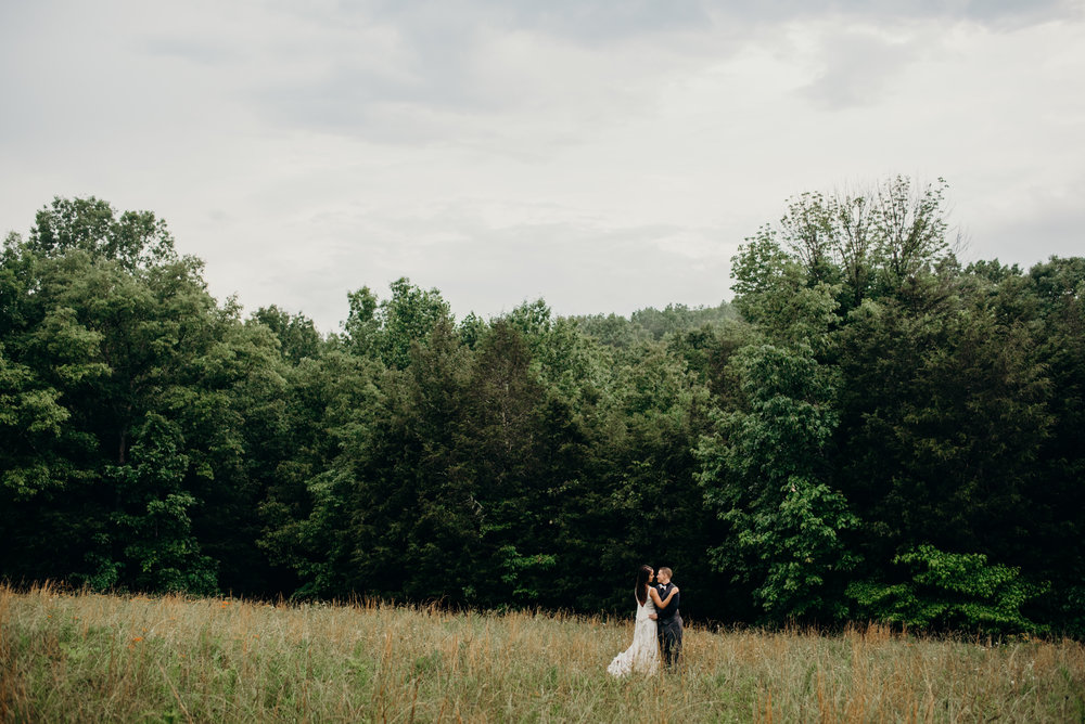 married couple in the distance embracing and looking at each other in a field surrounded by trees
