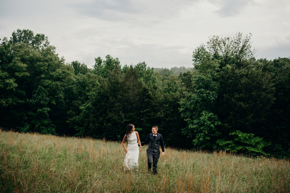 newlywed same-sex couple walking through field surrounded by trees