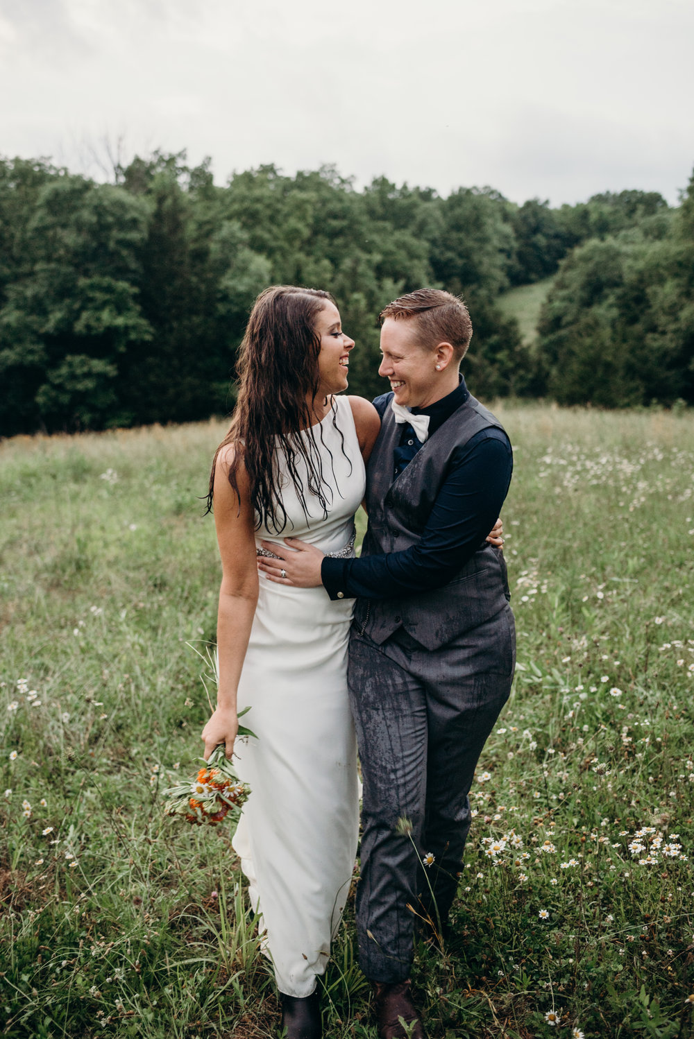 happy same-sex newlyweds embracing in Kentucky field after rainstorm