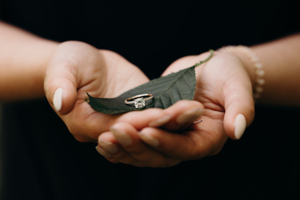 woman's hands holding a diamond engagement ring on top of a leaf