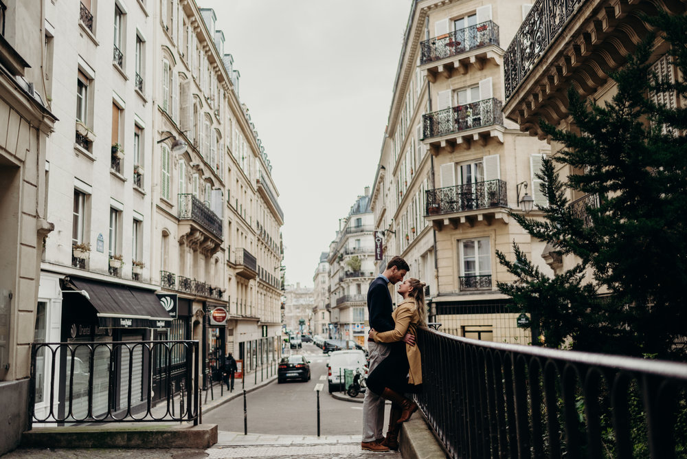 husband and wife embrace against railing on streets of Paris, France