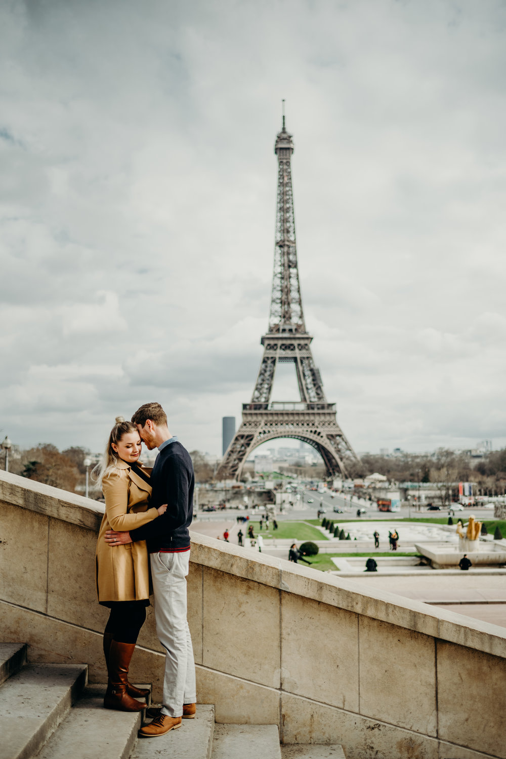 couple embrace on stairs in front of Eiffel Tower in Paris, France