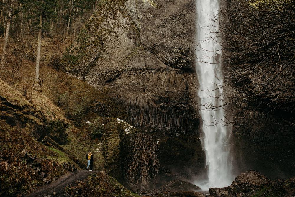 couple embraces underneath latourell falls waterfall outside of portland oregon